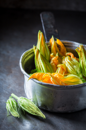 Closeup of fresh zucchini flower in metal pot