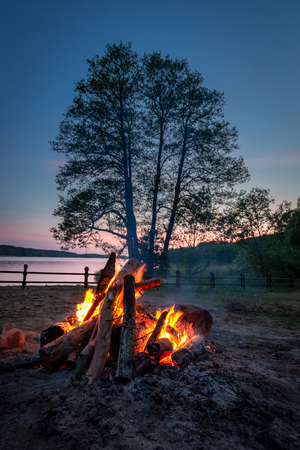 Amazing bonfire at dusk by the lake in summer