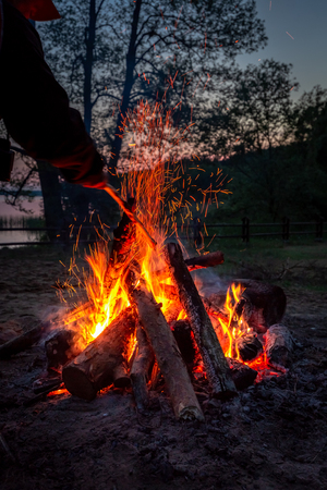 Beautiful bonfire at dusk by the lake in summer 写真素材