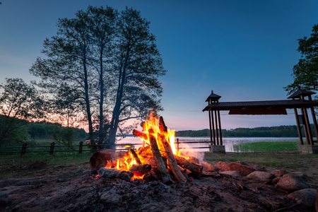 Warm bonfire at dusk by the lake in summer Stock fotó