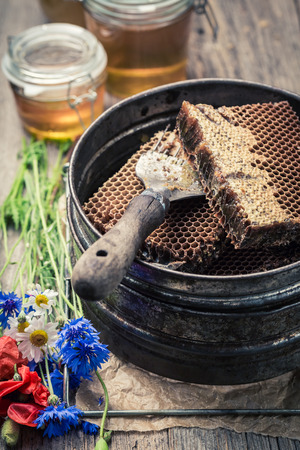 Closeup of tools for beekeeping with honeycombs, honey and hats Stock Photo