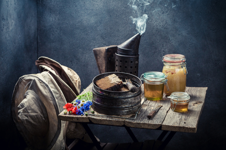 Fresh honey and rusty beekeeping tools on rustic table Stock Photo