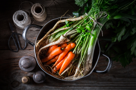 Ingredients for homemade vegan soup with parsley, carrots and leek Фото со стока