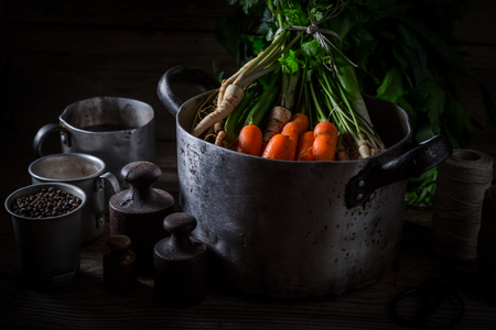 Ingredients for broth with carrots, parsley and leek in dark Фото со стока