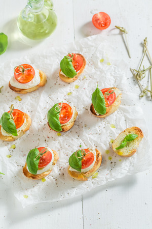 Delicious crostini made with mozzarella and tomato on white paper Banque d'images - 105088708