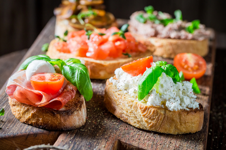 Delicious and tasty mix of bruschetta on old wooden table Stok Fotoğraf - 105088424