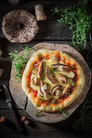 Homemade and tasty pizza on old wooden table