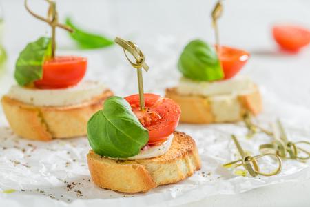 Closeup of crostini with mozzarella and tomato on white paper