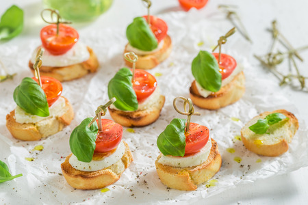 Crostini made with mozzarella and tomato on white paper