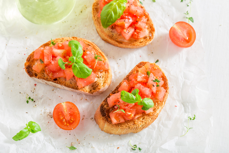 Bruschetta with tomato and basil on white table