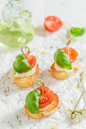 Homemade crostini with tomato and basil on white paper