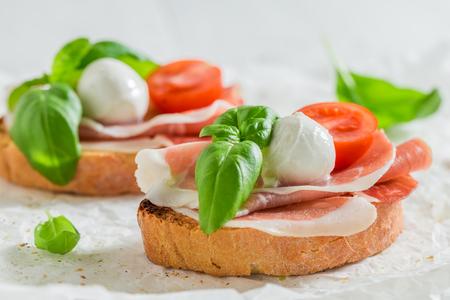 Bruschetta with prosciutto, tomato and mozzarella for a snack