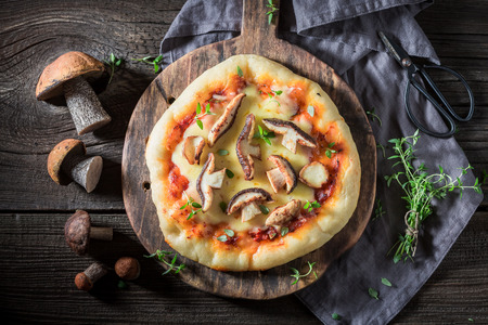 Wild and rustic pizza with noble mushrooms and herbs
