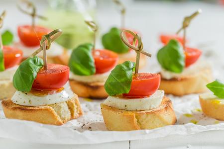 Closeup of crostini with tomato and mozzarella on white paper