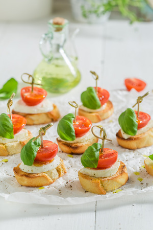 Homemade crostini with tomato, mozzarella and basil on white paper