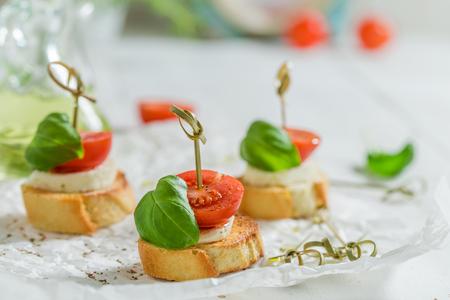 Tasty crostini made with mozzarella and tomato on white paper