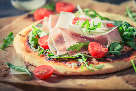 Delicious pizza with tomatoes, cheese and rucola