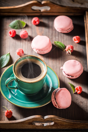 Coffee and delicious pink macaroons served with hot coffee