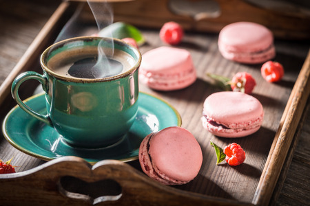 Hot coffee and tasty pink macaroons made of fresh raspberries
