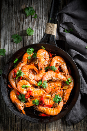 Top view of shrimps on pan with garlic and peppers Фото со стока