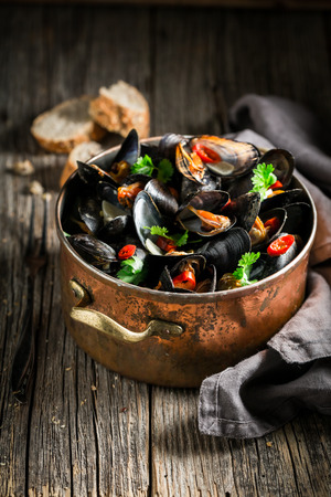 Tasty mussels served with wholemeal bread on wooden table