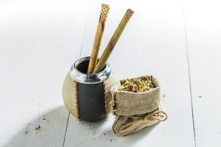 Yerba mate made of fresh dried leaves on white table