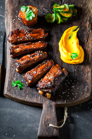 Delicious roasted ribs with vegetables and potato on old plank Stockfoto