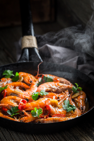 Tasty shrimps on pan with garlic and chilli peppers