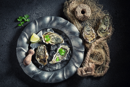 Top view of oysters with lemons on dark plate Stock Photo