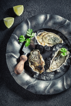Fresh and delicious oysters with lemons on dark plate