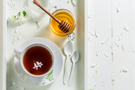 Hot tea with honey on white background