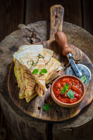 Closeup of spicy tortilla as quesadilla with sauce and herbs