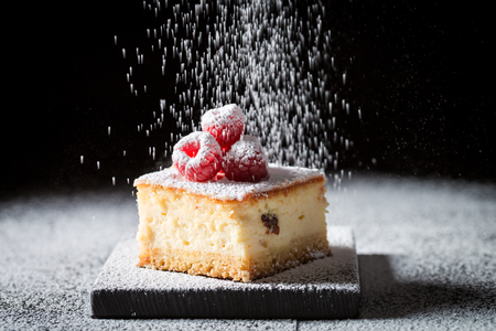 Falling powdered sugar on cheesecake with raspberries Stockfoto