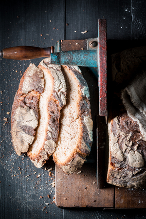Healthy loaf of bread on slicer on dark table Stockfoto - 106622570