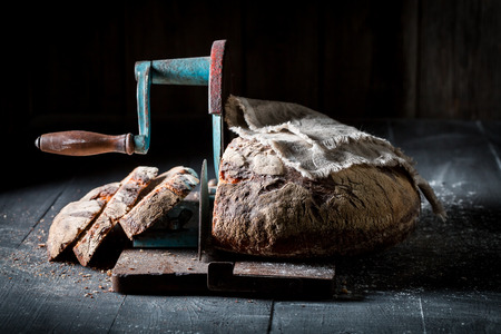 Rustic bread on slicer with flour and crumbs Stockfoto