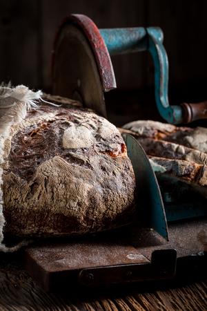 Closeup of tasty bread on slicer on dark table Stockfoto - 106622645