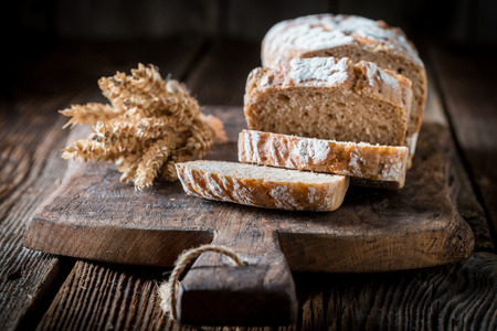 Tasty and fresh bread with grains on wooden table