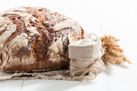 Loaf of bread with whole grains on white table