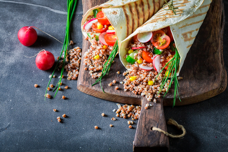 Tasty vegetarian tortilla with groats, radish and cherry tomatoes