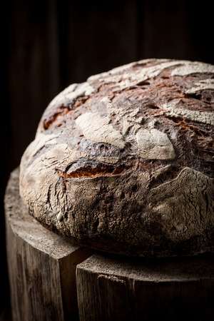 Tasty loaf of bread on old wooden stump Stockfoto