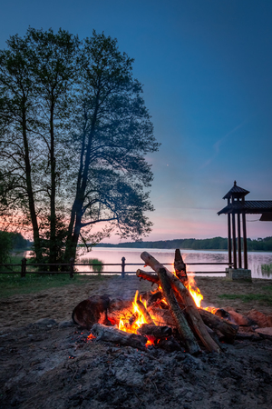 Calm bonfire at dusk by the lake in summer
