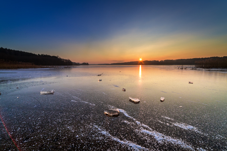 Piece of ice on frozen lake at sunset in winter