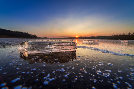 Cold piece of ice on lake at dawn in winter