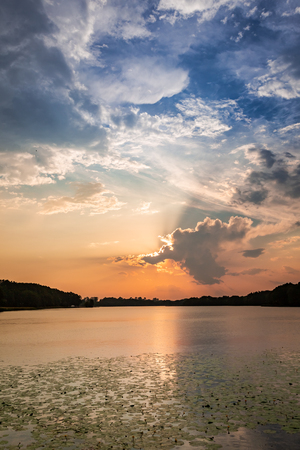 Calm sunset at the summer lake with dynamic clouds Stock Photo