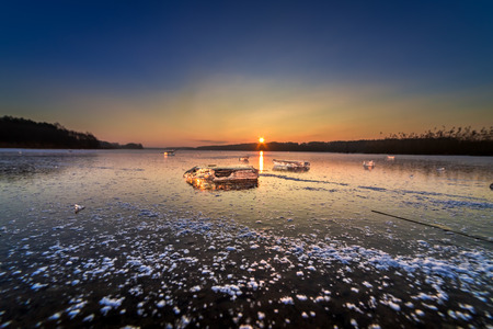 Frozen lake and piece of ice at sunset in winter