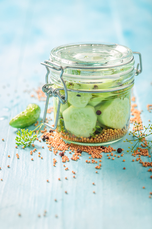 Homemade and tasty pickled cucumber on blue table