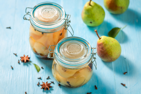 Homemade and healthy pickled pears on blue table Banco de Imagens - 107639903