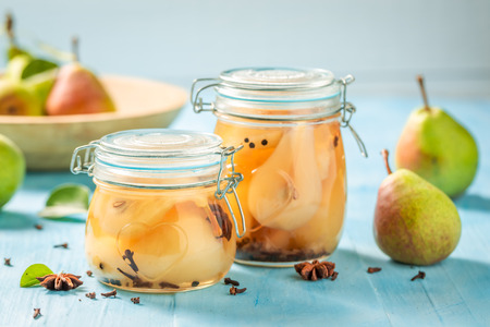 Natural and juicy pickled pears on blue table Banco de Imagens - 107639907