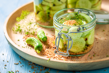 Natural and healthy canned cucumber on blue table
