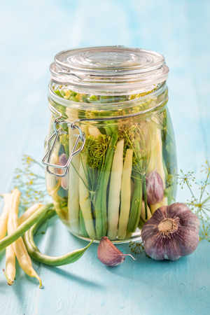 Homemade pickled green and yellow beans on blue table
